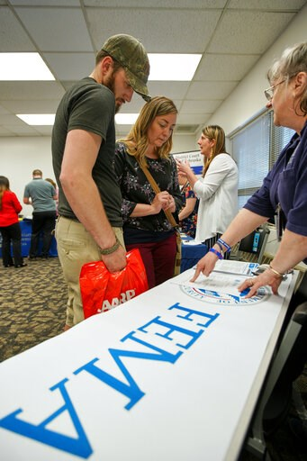 (AP Photo/Nati Harnik). In this April 25, 2019 photo, April Kleinschmit and her husband Brandon , talk to FEMA representative Kristina Pooler, right, about available FEMA jobs, at a job fair in Lincoln, Neb. With federal disaster recovery staffers scra...