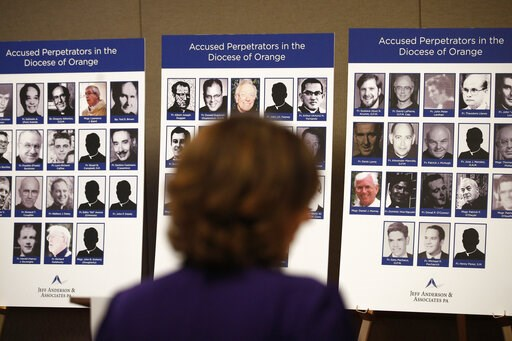 (AP Photo/Jae C. Hong). FILE - In this Thursday, Dec. 6, 2018 file photo, an advocate and survivor of sexual abuse looks at the photos of Catholic priests accused of sexual misconduct by victims during a news conference in Orange, Calif. As the U.S. Ca...