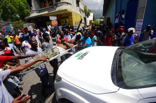 (AP Photo/Dieu Nalio Chery). Protesters carry the body of man to a police vehicle, shouting blame at the police for his death, during an anti-government protest in Port-au-Prince, Haiti, Sunday, June 9, 2019. Protesters denouncing corruption paralyzed ...
