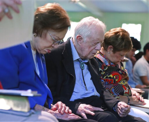 (Curtis Compton/Atlanta Journal-Constitution via AP). President Jimmy Carter and Rosalynn Carter bow their heads in prayer with members and visitors during the worship service at Maranatha Baptist Church less than a month after the 39th U.S. president ...