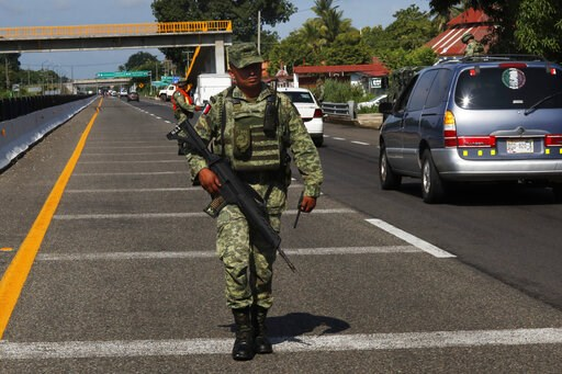 (AP Photo/Marco Ugarte). A Mexican Army soldier walks on the highway, near an immigration checkpoint in Tapachula, Chiapas state, Mexico, Saturday June 8, 2019.