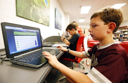 (AP Photo/Rogelio V. Solis). In this May 8, 2019, photo, third-grade student Miles Stidham uses an East Webster High School laptop to do homework in Maben, Miss. The Stidhams are unable to get internet at their home in the country, so they take advanta...