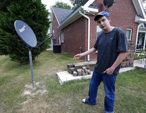 (AP Photo/Rogelio V. Solis). In this May 8, 2019, photo, Riley Shaw talks about his family's internet at his home outside Starkville, Miss. The satellite dish allows a certain amount of high-speed data each month and then slows to a crawl.