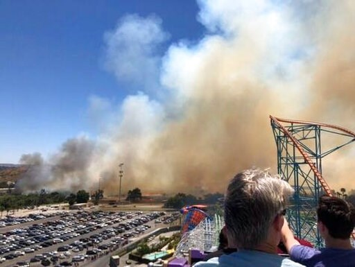 (Ryan Reede via AP). This photo provided by Ryan Reede shows smoke from a fast-moving brush fire that Reede took as he was riding on a roller coaster at Six Flags in Valencia, north of Los Angeles. The brush fire erupted near the huge amusement and wat...
