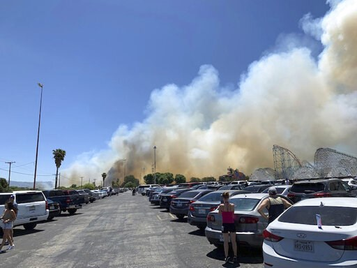 (Joel Cannon via AP). In this Sunday, June 9, 2019, photo provided by Joel Cannon, heavy smoke from a fast-moving brush fire surrounds Six Flags Magic Mountain and Hurricane Harbor, in Santa Clarita, Calif.