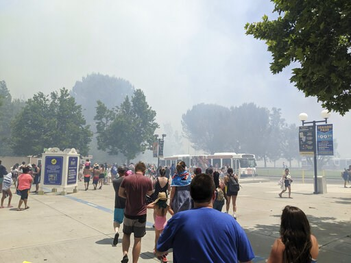 (Arthur Wilkie via AP). In this photo provided by Arthur Wilkie, people evacuate Six Flags Magic Mountain and Hurricane Harbor, Sunday, June 9, 2019, in Santa Clarita, Calif., north of Los Angeles, as smoke from a fast-moving brush fire surrounded the ...