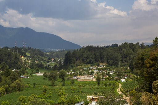 (AP Photo/Moises Castillo). In this June 8, 2019 photo, La Union Los Mendez village is seen from the community council building in the mountain hamlet of San Juan Ostuncalco, Guatemala. About one in three people has migrated from the town, according to...
