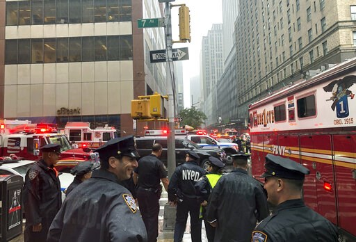(AP Photo/Mark Lennihan). New York police officers monitor the streets near 51st Street and 7th Avenue, Monday, June 10, 2019, in New York, where a helicopter was reported to have crash landed on top of a building in midtown Manhattan.