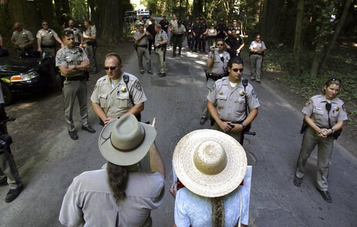 (Kent Porter/The Press Democrat via AP, File). FILE - In this July 22, 2006 file photo, protesters Gary and Janet Evans of Sebastopol, Calif., try to talk with California Highway Patrol officers and Sonoma County Sheriff's deputies as they block off th...