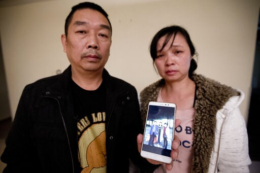 (AP Photo/Michael Conroy File). FILE- In this Nov. 1, 2017 file photo, Ronggao Zhang, left, and Lifeng Ye, display a photo them with their missing daughter, Yingying Zhang, in Urbana, Ill. Almost two years after their daughter disappeared from the Univ...