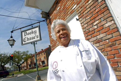 (AP Photo/Cheryl Gerber, File). FILE - In this March 9, 2007 file photo, Chef Leah Chase stands outside her famous Creole restaurant, Dookie Chase's, which was flooded out during Hurricane Katrina, in New Orleans. Family, friends and admirers of Chase ...