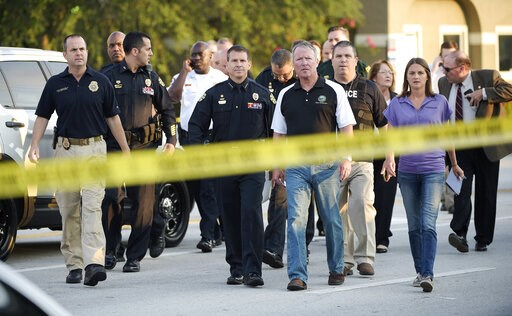 (AP Photo/Phelan M. Ebenhack). FILE - In this Sunday, June 12, 2016 file photo, Mayor Buddy Dyer, center right, and then-Police Chief John Mina, center left, arrive for a news conference after the mass shooting at the Pulse Orlando nightclub in Orlando...