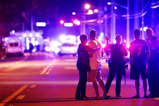 (AP Photo/Phelan M. Ebenhack, File). FILE - In this June 12, 2016 file photo, an Orlando Police officer directs family members away from a mass shooting at the Pulse nightclub in Orlando, Fla., that left 49 people dead. The shooter was killed by police...