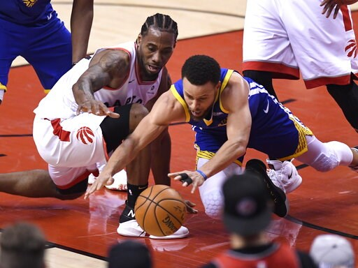 (Frank Gunn/The Canadian Press via AP). Toronto Raptors forward Kawhi Leonard (2) and Golden State Warriors guard Stephen Curry (30) vie for the ball during first-half basketball action in Game 5 of the NBA Finals in Toronto, Monday, June 10, 2019.
