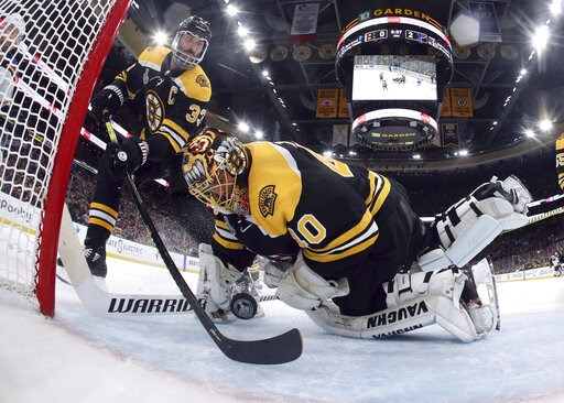 (Bruce Bennett/Pool via AP). Boston Bruins' Zdeno Chara, left, of Slovakia, reaches behind goaltender Tuukka Rask, of Finland, to keep the puck from crossing the goal line during the second period in Game 7 of the NHL hockey Stanley Cup Final against t...