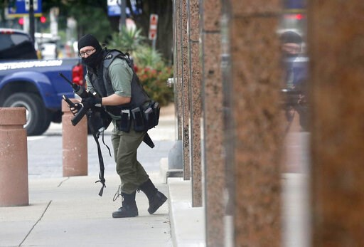 An armed shooter stands near the Earle Cabell Federal Building Monday, June 17, 2019, in downtown Dallas. (Tom Fox/The Dallas Morning News via AP)