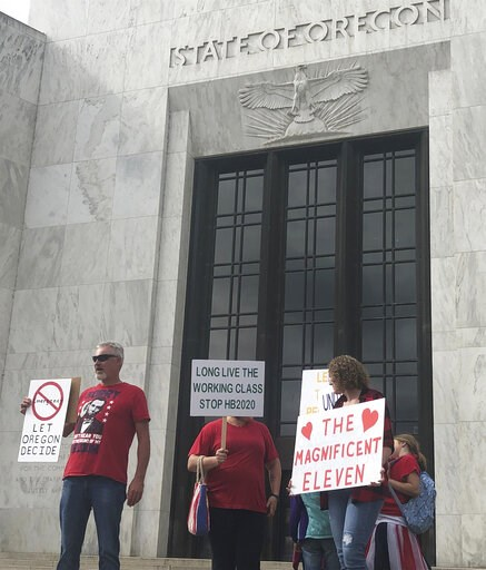 (AP Photo/Sarah Zimmerman). In this photo taken Sunday, June 23, 2019, a small crowd of local Republicans show their support of a Republican walkout outside the Oregon State Capitol in Salem, Ore. The gathering took place only a day after the Senate Pr...