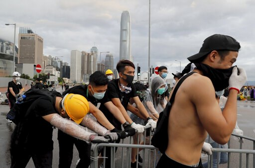 Protesters push a barrier to position as they attempt to block a ceremony in Hong Kong on Monday, July 1, 2019.  (AP Photo/Kin Cheung)
