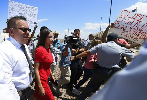 (Briana Sanchez/El Paso Times via AP). U.S. Rep. Alexandria Ocasio-Cortez, D-New York, is escorted back to her vehicle after she speaks at the Border Patrol station in Clint, Texas, about what she saw at area border facilities Monday, July 1, 2019.