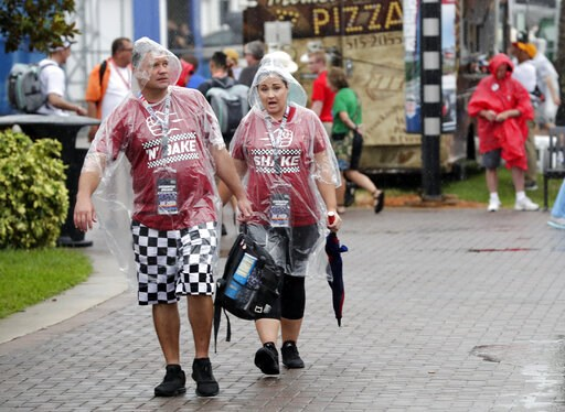 (AP Photo/John Raoux). Fans walk through the Fan Zone during a weather delay of activities before the NASCAR Cup Series auto race at Daytona International Speedway, Saturday, July 6, 2019, in Daytona Beach, Fla.
