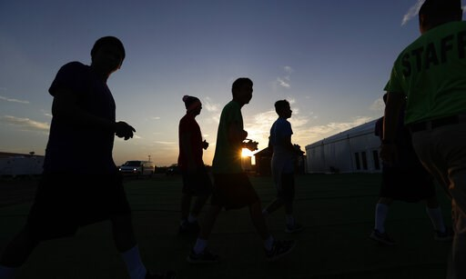 (AP Photo/Eric Gay). In this Tuesday, July 9, 2019, photo, at sunrise, immigrants are escorted to a tent that serves a dining hall for the U.S. government's newest holding center for migrant children in Carrizo Springs, Texas. The Department of Health ...