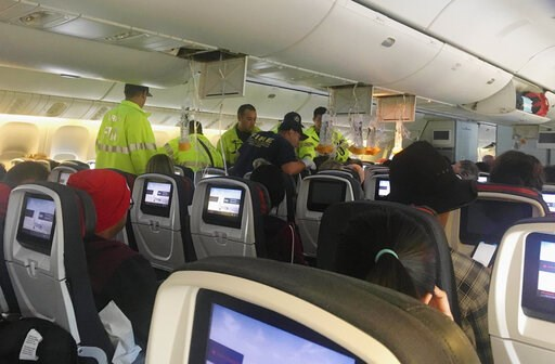 (Tim Tricky/Hurricane Fall via AP). In this photo provided by Hurricane Fall, responders treat a passenger on an Air Canada flight to Australia that was diverted and landed at Daniel K. Inouye International Airport in Honolulu on Thursday, July 11, 201...