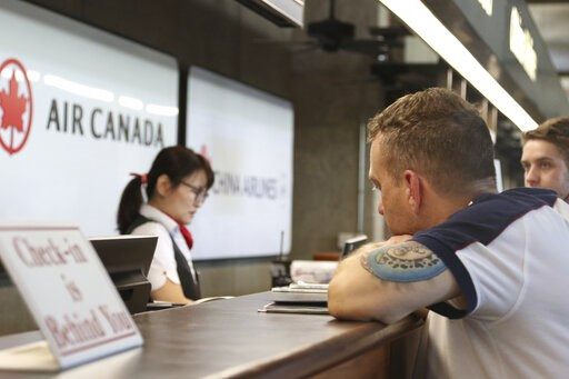 (AP Photo/Caleb Jones). Andrew Szucs, right, who was on the Air Canada flight that made an emergency landing, waits for assistance at the Air Canada desk, Thursday, July 11, 2019 at Honolulu's international airport. Intense turbulence struck an Air Can...