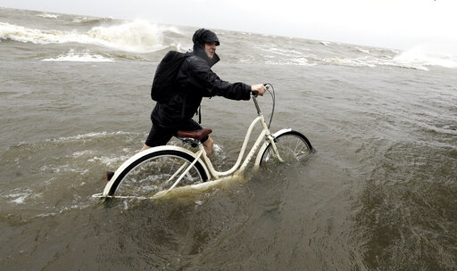(AP Photo/David J. Phillip). Tyler Holland guides his bike through the water as winds from Tropical Storm Barry push water from Lake Pontchartrain over the seawall Saturday, July 13, 2019, in Mandeville, La.