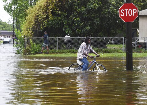 (Henrietta Wildsmith/The Shreveport Times via AP). A man tries to bike through the flooding from the rains of storm Barry on LA Hwy 675 in New Iberia, La., Sunday, July 14, 2019. Tropical Depression Barry dumped rain as it slowly swept inland through G...