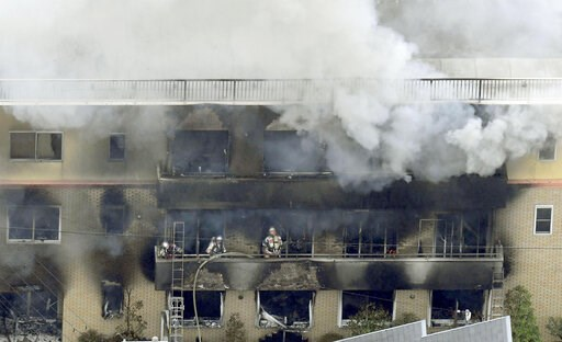 (Kyodo News via AP). Firefighters work as smoke billows from a three-story building of Kyoto Animation in a fire in Kyoto, western Japan, Thursday, July 18, 2019. Kyoto prefectural police said the fire broke out Thursday morning after a man burst into ...