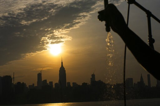 (AP Photo/Eduardo Munoz Alvarez). The sun rises over New York City and the Empire State Building while a man sprays water at Pier A on Saturday, July 20, 2019 in Hoboken, N.J. Temperatures in the high 90s are forecast for Saturday and Sunday with a hea...