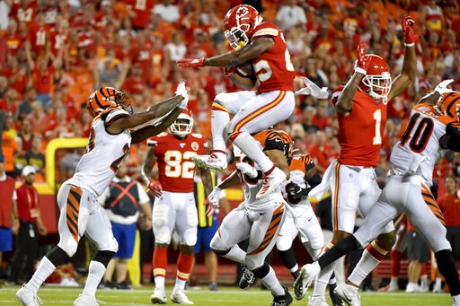 (AP Photo/Ed Zurga). Kansas City Chiefs running back Darwin Thompson, center, is about to land on Cincinnati Bengals cornerback Darius Phillips, left, after trying to vault over  Bengals safety Brandon Wilson, right, a during the second half of an NFL ...