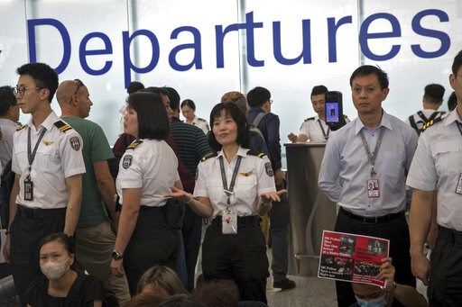 (AP Photo/Vincent Thian). An airport security staff member gestures to travelers at the Hong Kong International Airport in Hong Kong, Tuesday, Aug. 13, 2019. Protesters clogged the departure area at Hong Kong's reopened airport Tuesday, a day after the...