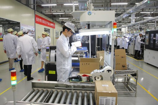 (AP Photo/Kin Cheung, File). FILE - In this March 6, 2019, file photo a staff member works on a mobile phone production line during a media tour in Huawei factory in Dongguan, China's Guangdong province. Huawei Technologies Co. is one of the world's bi...