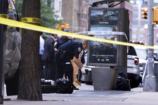 (AP Photo/Kevin Hagen). An investigator picks up a suspicious package that was thought to be an explosive device in Manhattan's Chelsea neighborhood Friday, Aug. 16, 2019, in New York.  The appliance was deemed harmless and taken away as evidence. .