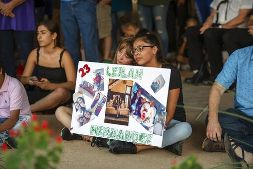 (Jacy Lewis/Reporter-Telegram via AP). Celeste Lujan, left, and Yasmin Natera hold a sign in honor of Leilah Hernandez during a vigil for victims of the shooting spree the day before, Sunday, Sept. 1, 2019, at the University of Texas of the Permian Bas...