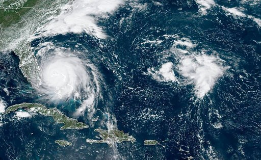 (NOAA via AP). This GOES-16 satellite image taken Monday, Sept. 2, 2019, at 16:40 UTC and provided by National Oceanic and Atmospheric Administration (NOAA), shows Hurricane Dorian, left, churning over Bahamas. Hurricane Dorian hovered over the Bahamas...