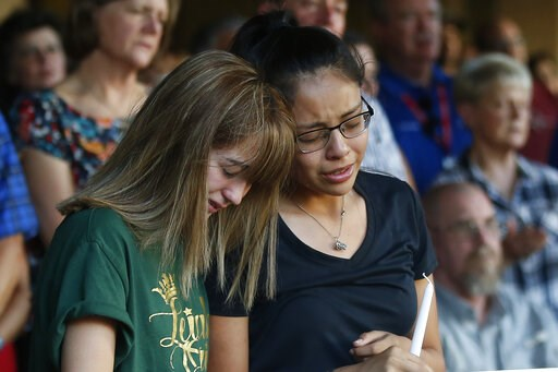(AP Photo/Sue Ogrocki). CORRECTS SPELLING OF VICTIM'S FIRST NAME TO LEILAH INSTEAD OF LEILA - High School students Celeste Lujan, left, and Yasmin Natera mourn their friend Leilah Hernandez, one of the victims of the Saturday shooting in Odessa, at a m...