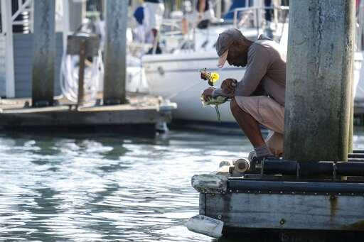 (AP Photo/Ringo H.W. Chiu). James Miranda, right, of Santa Barbara, holds flowers and takes a moment to reflect at a dock near the Sea Landing at Santa Barbara Harbor in Santa Barbara, Calif., Monday, Sept. 2, 2019. A fire raged through a boat carrying...