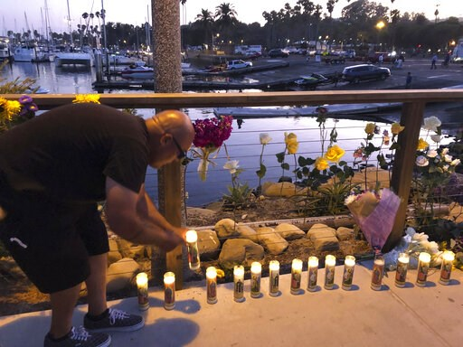 (AP Photo/Stefanie Dazio). Orlando Aldana, 42, of Santa Barbara, lights candles in honor of the victims at the growing memorial for those caught in the fire on the Conception boat, Monday, Sept. 2, 2019, in Santa Barbara, Calif. A fire raged through th...