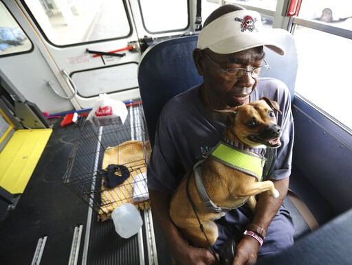 (Curtis Compton/Atlanta Journal-Constitution via AP). Eddie Wright, 68, and his dog Vino wait on one of the final buses at Lanier Plaza in Brunswick, Ga., to evacuate from Hurricane Dorian.