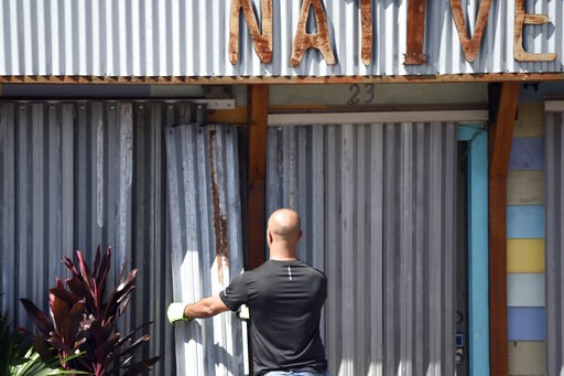 (AP Photo/Meg Kinnard). A worker affixes corrugated metal to the front of a business along the main drag in Folly Beach, S.C., on Tuesday, Sept. 3, 2019. Businesses and residents throughout the Charleston area continued to prepare structures for the ar...
