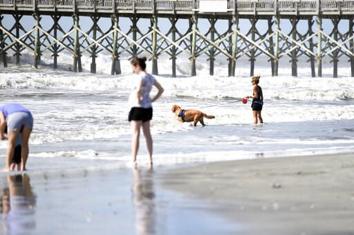 (AP Photo/Meg Kinnard). People walk near the pier at Folly Beach, S.C.,, Tuesday, Sept. 3, 2019, ahead of the arrival of Hurricane Dorian. The storm weakened to a Category 2 storm on Tuesday as it continued to batter the Bahamas with life-threatening s...