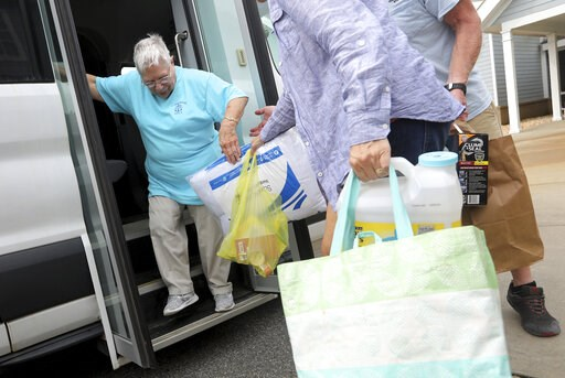 (Steve Earley/The Virginian-Pilot via AP). Lin Henderson gets help as she moves her belongings from a Dare County Transportation Bus to another bus as she evacuates from Hatteras Island on Wednesday, Sept. 4, 2019. Mandatory evacuation plans have been ...