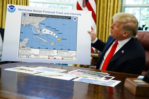 (AP Photo/Evan Vucci). President Donald Trump holds a chart as he talks with reporters after receiving a briefing on Hurricane Dorian in the Oval Office of the White House, Wednesday, Sept. 4, 2019, in Washington.