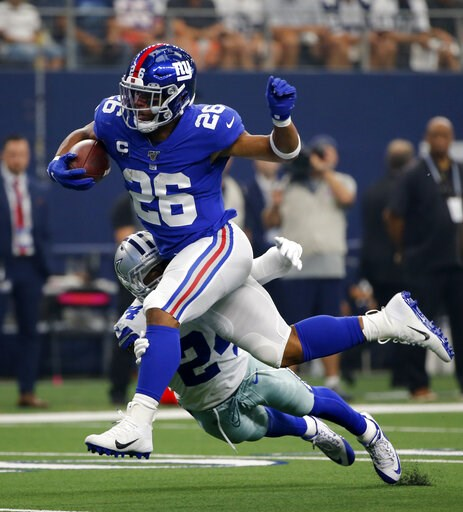 (AP Photo/Michael Ainsworth). New York Giants running back Saquon Barkley (26) attempts to escape the tackle by Dallas Cowboys cornerback Chidobe Awuzie (24) in the first half of a NFL football game in Arlington, Texas, Sunday, Sept. 8, 2019.