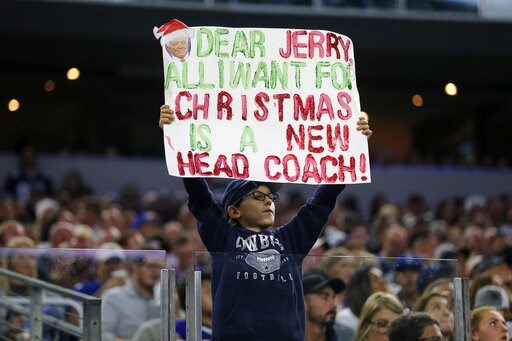 (AP Photo/Michael Ainsworth). A young fan holds up a sign asking Dallas Cowboys team owner Jerry Jones for a new head coach in the first half of an NFL football game against the Buffalo Bills in Arlington, Texas, Thursday, Nov. 28, 2019.