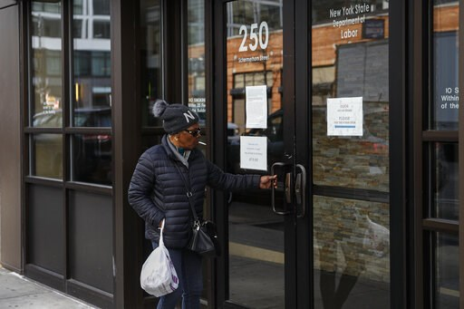 (AP Photo/John Minchillo). Visitors are unable to gain access to the Department of Labor due to closures over coronavirus concerns, Wednesday, March 18, 2020, in New York. Applications for jobless benefits are surging in some states as coronavirus conc...