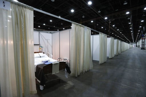 (AP Photo/Carlos Osorio). This photo shows a hospital bed in one of the temporary rooms at the TCF Center, Monday, April 6, 2020, in Detroit. The city's convention center was converted to accommodate an overflow of patients with the coronavirus. The U....